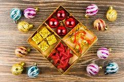 Caixa com bolas, caixa de cartão, estrelas e sinos, bolas do Natal Imagens de Stock