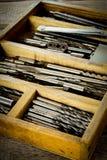 Caixa com brocas em um fundo de madeira fotografia de stock