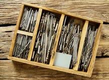 Caixa com brocas em um fundo de madeira imagem de stock
