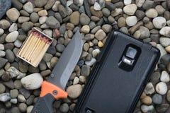 Caixa com fósforos, a faca de dobramento e o smartphone Foto de Stock Royalty Free