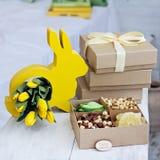 Caixa com porcas e frutos secados Tabela da Páscoa Coelhinho da Páscoa amarelo, ramalhete de tulipas amarelas fotos de stock