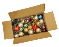 Caixa com um ouropel do Natal e uns brinquedos de ano novo. Foto de Stock