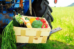 Caixa com vegetais ao lado de um trator fotos de stock royalty free
