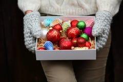 Caixa completa de decorações do Natal na mão do ` s da mulher Fotografia de Stock Royalty Free