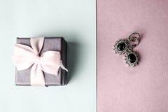 Caixa da beleza, caixa de presente bonita festiva com uma curva com os brincos de prata com pedras preciosas em um fundo roxo e a imagem de stock royalty free