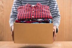Caixa da doação para pobres com roupa nas mãos masculinas Fotos de Stock Royalty Free