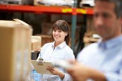 Caixa da exploração do trabalhador de In Warehouse With do gerente no primeiro plano Fotografia de Stock Royalty Free
