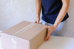 A caixa da fita da colagem do homem novo e toma o pacote nas mãos, estando em P Imagem de Stock
