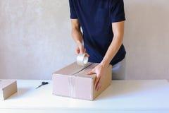 A caixa da fita da colagem do homem novo e toma o pacote nas mãos, estando em P Fotos de Stock Royalty Free