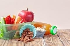 Caixa de almoço escolar com sanduíche, vegetais, suco e amêndoas na tabela imagens de stock royalty free