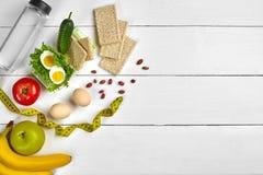 Caixa de almoço saudável do vegetariano Ovos, vegetais, frutos e garrafa da água no fundo de madeira branco Vista superior com có Foto de Stock
