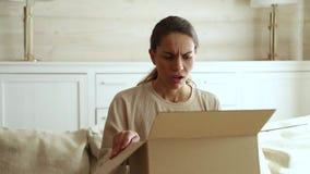 Caixa de cartão aberta descontentada do cliente fêmea para receber o pacote danificado vídeos de arquivo