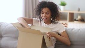 Caixa de cartão aberta do cliente africano feliz da mulher que senta-se no sofá video estoque