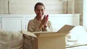 Caixa de cartão aberta entusiasmado do consumidor de jovem mulher para obter o pacote postal video estoque