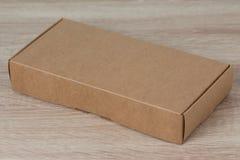 Caixa de cartão ou caixa de papel marrom no fundo de madeira Imagem de Stock