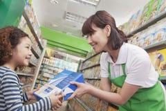 Caixa de cereal fêmea de Gives Little Girl do caixeiro das vendas fotos de stock