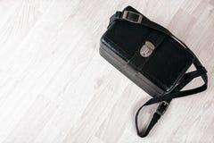 Caixa de couro preta do vintage em um assoalho de madeira Fotos de Stock