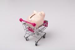 Caixa de dinheiro do porco no carrinho de compras no fundo branco imagens de stock royalty free