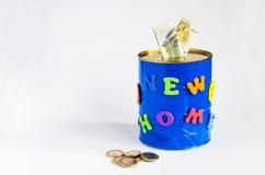 Caixa de dinheiro feito a mão com inscrição home nova, cédulas do Euro e algumas moedas Fundo branco Imagens de Stock Royalty Free