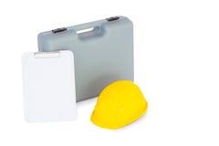 Caixa de ferramentas, capacete de segurança e prancheta no fundo branco Imagem de Stock