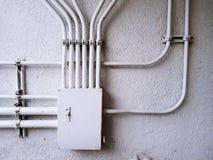 Caixa de junção elétrica branca do controle para a linha elétrica da distribuição no muro de cimento branco com o espaço da cópia foto de stock royalty free