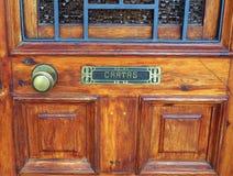 Caixa de letra e botão de porta de bronze na porta de madeira, Figueres, Espanha foto de stock