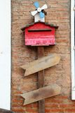 Caixa de letra de madeira vermelha sob a turbina e?lica pequena na parede de tijolo imagem de stock royalty free