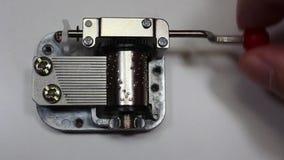Caixa de música no fundo branco, dedos que giram a alavanca O macro do mecanismo e das engrenagens da caixa de música que giram c vídeos de arquivo