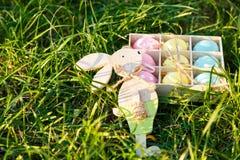 Caixa de madeira com mentiras pintados à mão do rosa, as amarelas e as azuis dos ovos na grama verde da mola na luz solar Páscoa  fotos de stock royalty free