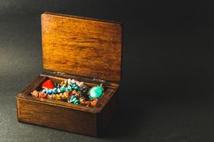 Caixa de madeira completamente da joia colorida no fundo cinzento escuro Foto de Stock