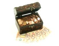 Caixa de madeira completamente das moedas em notas de banco do euro Foto de Stock