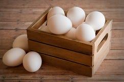 Caixa de madeira de ovos frescos em uma placa de madeira do fundo da prancha Imagem de Stock Royalty Free