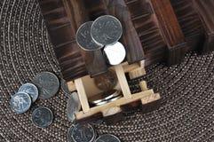 Caixa de madeira e moedas no intertexture da grama Imagens de Stock Royalty Free
