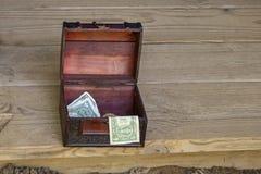 Caixa de madeira ornamentado da ponta com os dólares americanos que sentam-se na borda da fase de madeira rústica fotografia de stock