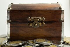 Caixa de madeira velha com moedas imagem de stock