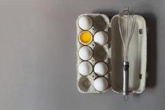 Caixa de ovos da galinha e de batedor de ovos crus do metal no fundo cinzento B fotos de stock