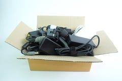 Caixa de papel com o carregador usado danificado ou velho do poder do adaptador do laptop ou de dispositivos bondes no branco fotos de stock