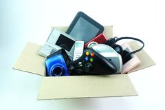 Caixa de papel com os dispositivos usados danificados ou velhos da eletrônica para o uso diário no fundo branco fotografia de stock