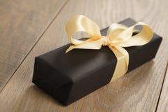 Caixa de papel do preto feito a mão do presente com curva amarela da fita na tabela de madeira Fotos de Stock Royalty Free