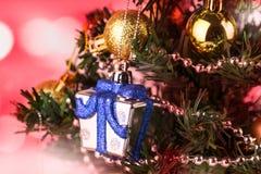 A caixa de prata do close-up decora em uma árvore de Natal com ornamento, fundo vermelho do bokeh do tom imagens de stock