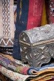 Caixa de prata ornamentado do trinket com as matérias têxteis coloridas na venda em um mercado marroquino Foto de Stock