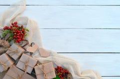 Caixa de presente de época natalícia e bagas vermelhas no fundo de madeira Packagin Imagens de Stock