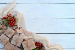 Caixa de presente de época natalícia e bagas vermelhas no fundo de madeira Papel de embrulho e guita de empacotamento das fitas Imagem de Stock