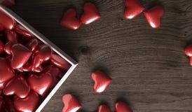Caixa de presente aberta completamente de corações na superfície escura da madeira Imagem de Stock Royalty Free