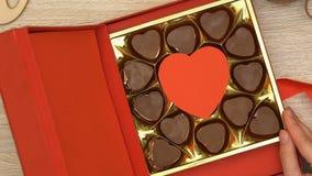Caixa de presente aberta da mulher com o afrodisíaco coração-dado forma dos doces de chocolate, vista superior vídeos de arquivo
