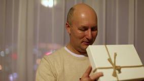 Caixa de presente aberta do homem caucasiano adulto feliz Luzes de cintilação em sua cara Fulgor alaranjado O homem na camiseta o video estoque