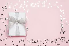 Caixa de presente agradável com curva no fundo cor-de-rosa com estrelas de prata Copyspace Espaço livre para seu texto Vista supe Fotos de Stock Royalty Free