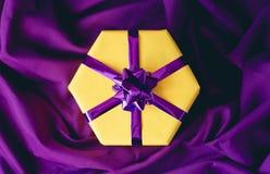 Caixa de presente amarela com uma curva roxa fotografia de stock royalty free