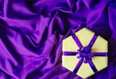 Caixa de presente amarela com uma curva roxa fotografia de stock
