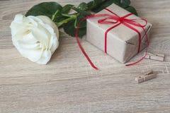 Caixa de presente amarrada com fita vermelha, rosa do branco no fundo de madeira fotos de stock